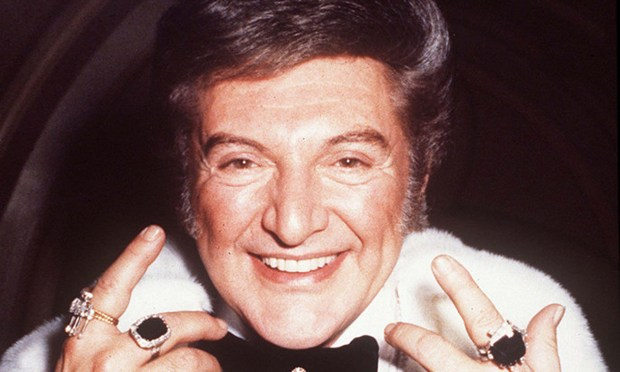 "Pianist and singer Liberace was born on this day in 1919 in West Allis, Wis., (as evidenced by his sartorial splendor) and died in 1987. His image is back in the spotlight again in director Steven Soderbergh's HBO movie ""Behind the Candelabra,"" in which actor Michael Douglas portrays Liberace and Matt Damon his much younger lover. Liberace is pictured in 1977rings worth 110,000 Pounds Sterling (a British report), and his wristwatch in gold and diamond in the shape of a grand piano worth 14,000 Pounds Sterling. (Associated Press file photo)"