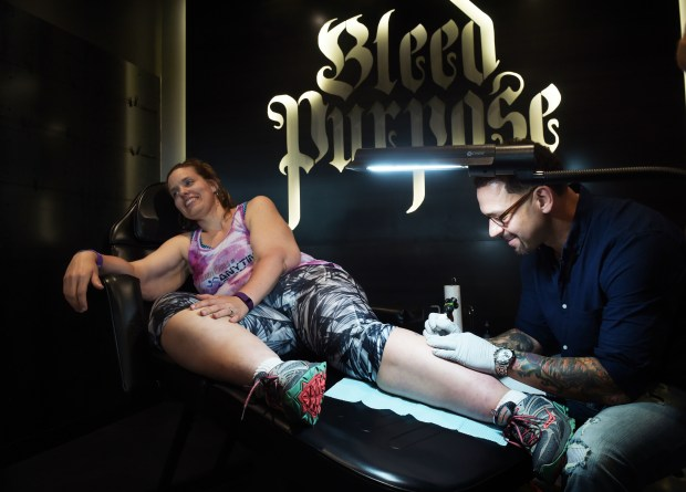 Cindy Keen of New London, Mn., featured in an inspirational video, has a tattoo drawn on her calf by Jimmy Hayden, as Anytime Fitness held a grand opening of their new corporate building in Woodbury Wednesday, May 25, 2016. (Pioneer Press: Scott Takushi)