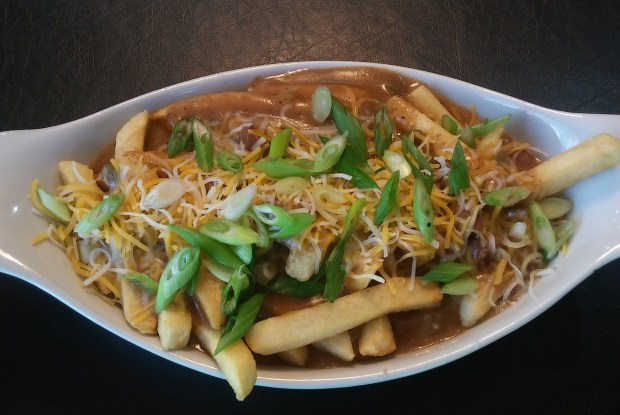 Gumbo frites: A bed of crispy french fries topped with Ragin's traditional New Orleans gumbo made with andouille sausage, chicken, bell peppers, onions, celery and a rich roux-based sauce, then finished off with cheese and green onions. At Ragin Cajun in The Garden, west wall. (Courtesy of Minnesota State Fair)