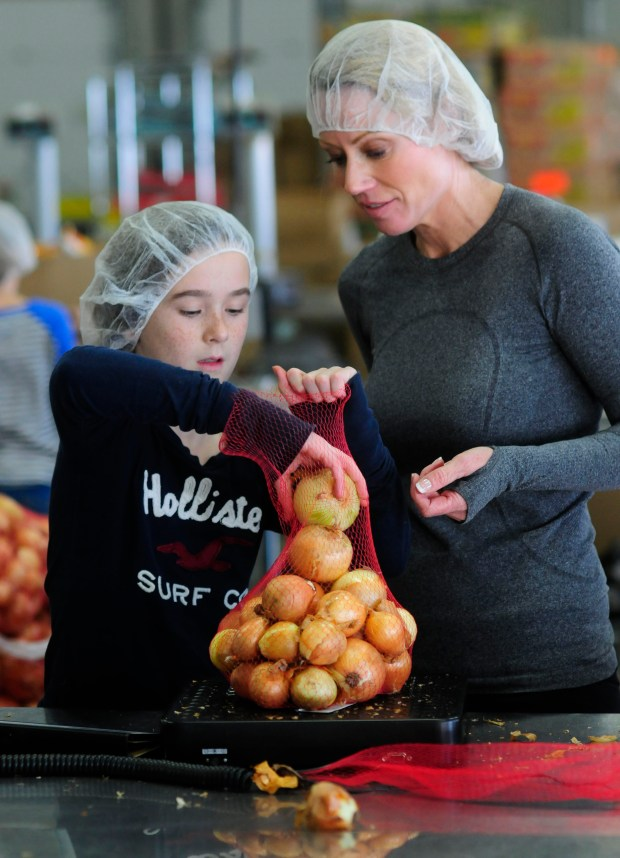 Janine Larson and her daughter Coco bagged and weighed onions as one hundred fifth graders from Edina's Normandale Elementary School volunteered at Second Harvest's packing facility in Golden Valley, Mn. on  December 21, 2012.   (Pioneer Press: Scott Takushi)