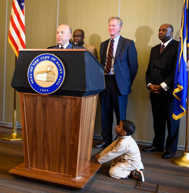 Sayfuddin Mohamud, 5, listens at the base of the podium as new St. Paul Police Chief Todd Axtell speaks during a new conference in St. Paul on Monday, June 13, 2016. Sayfuddin is the son of Imam Dr. Hassan Mohamud, behind Axtell. St. Paul Mayor Chris Coleman named Axtell as the news police chief Monday. The city council will vote on whether to confirm Axtell as chief on June 22. If approved, he would start in his new position the following day. (Special to the Pioneer Press: Craig Lassig)