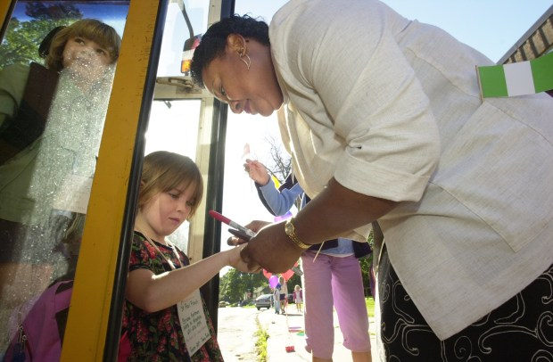 Principal Fatima Lawson greets first-graders at French Immersion School in St. Paul as they get off the bus, and she writes the bus number on Briana Hartman's hand on the first day of school on Sept. 3, 2002. (Pioneer Press file photo)