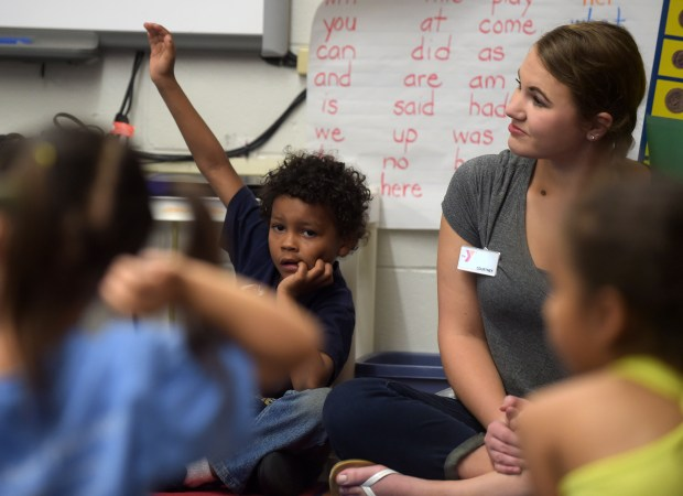 YMCA staffer Courtney Baeyen sits with Tawon George in a kindergarten class at L.C. Elementary School, where she works with children from a low-income apartment complex in Maplewood, Tuesday, May 31, 2016. The YMCA gives special attention to the kids, walking with them half a mile to school, helping in the classrooms, playground and cafeteria, and then running a program back home after school until 6 pm. (Pioneer Press: Scott Takushi)