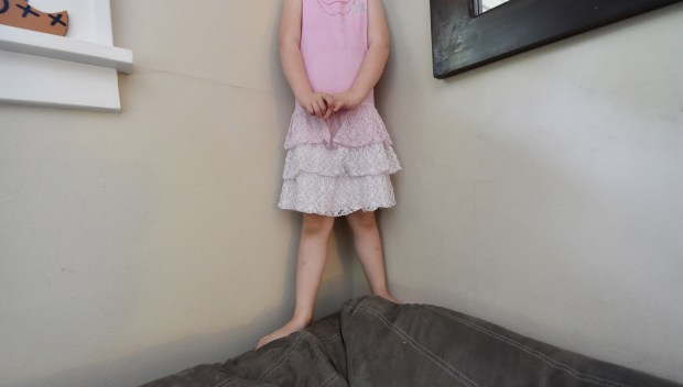 H stands on the back of the couch before launching herself off as she plays at home. She's often a blur in family photos because she's always singing, dancing, twirling, jumping. (Pioneer Press: John Autey)