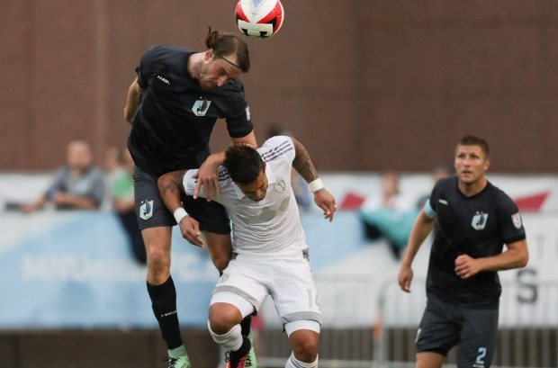 Minnesota United FC defender Brent Kallman heads the ball away from Sporting Kansas City forward Dom Dwyer on Wednesday night in a fourth-round match of the U.S. Open Cup soccer tournament at the National Sports Center in Blaine. (Photo courtesy of Minnesota United)
