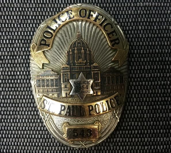 "A St. Paul officer's badge is bent, at top left, when someone threw a rock from a pedestrian bridge over I-94 the night before, Police Chief Todd Axtell showed on July 10, 2016. The rock hit an officer ""with enough force to crack helmets and bend a piece of solid steel like this,"" Axtell said. (Pioneer Press: Mara Gottfried)"