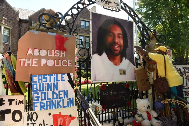 King Demetrius Pendleton hangs a sign on the gate of the Governor's Residence as protesters demonstrate against the police shooting and killing of Philando Castile and other people of color, shutting down Summit Avenue Sunday afternoon, July 24, 2016. ( Pioneer Press: Scott Takushi)