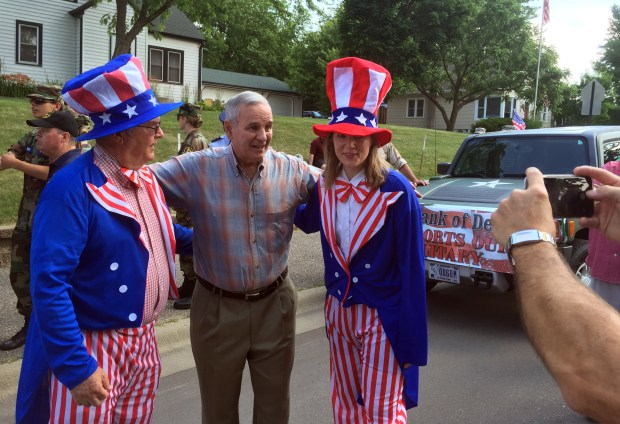 Gov. Mark Dayton has his photo taken with Steve and Wendy Gilmer, father and daughter, wearing patriotic costumes during the Fourth of July parade in Delano, Minn. on Monday, July 4, 2016. Dayton was the grand marshal for Delano's 2016 4th of July parade. Steve is the CEO of the State Bank of Delano and Wendy is the bank president. (Pioneer Press: Rachel E. Stassen-Berger)