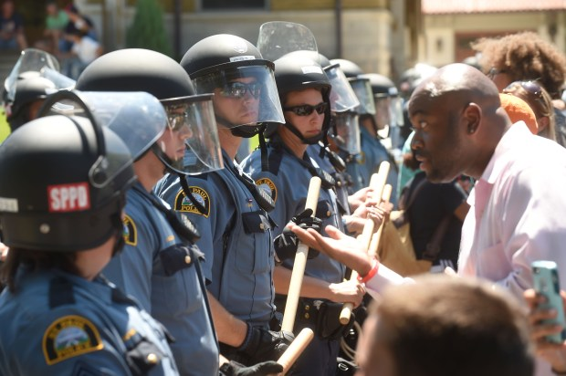 Jason Sole speaks to St. Paul police as they form a line across Summit Ave., a block from the Governor's Residence, in St. Paul on Tuesday, July 26, 2016. (Pioneer Press: Scott Takushi)