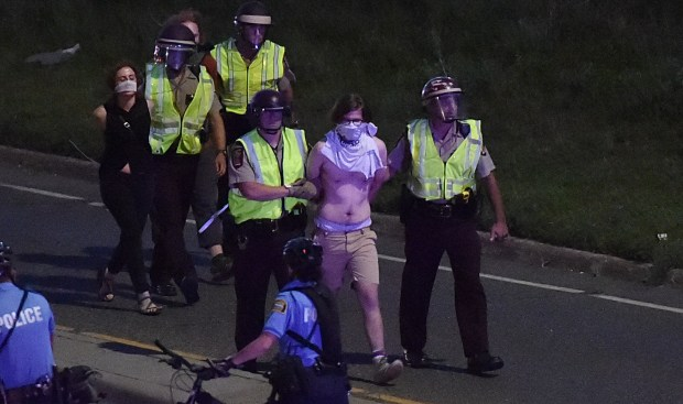 Minnesota State Patrol troopers arrest demonstrators as Black Lives Matter protesters shutdown interstate 94 in St. Paul between Dale Street and Lexington Avenue on Saturday, July 9, 2016. (Pioneer Press: John Autey)