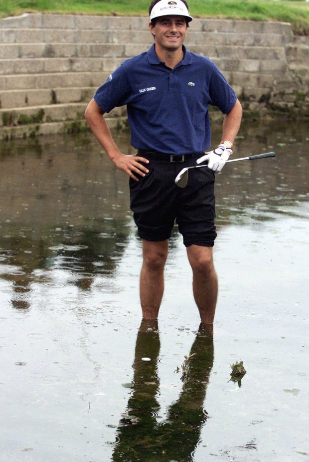 France's Jean Van de Velde smiles as he stands in the water of the Barry Burn that crosses the 18th fairway to see if his ball, bottom center, was playable during the final round of the 128th British Open Golf Championship at Carnoustie, Scotland, July 18, 1999. Van de Velde went on to make triple bogey and lose the Open in a playoff. But he hasn't stopped smiling since, a trait that has endeared him to fans and given his golfing career a major boost. (AP Photo/Str)