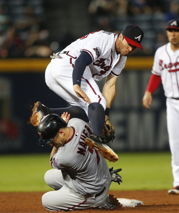 Atlanta Braves shortstop Chase d'Arnaud comes down on top of Minnesota Twins' Joe Mauer (7) as he turns a double play on a Trevor Plouffe ground ball during the sixth inning of a baseball game in Atlanta, Tuesday, Aug. 16, 2016, (AP Photo/John Bazemore)