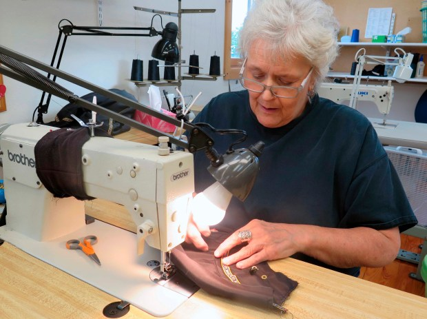 "In this Wednesday, July 27, 2016. photo, Mary Lou Korpela works on a shell anorak at the offices of Wintergreen Northern Wear in downtown Ely, Minn. The company employs 20 full-time workers. Co-owner Paul Schurke calls it an example of Ely's ""high quality, small batch"" manufacturing culture that also includes Crapola! granola and Steger Mukluks. While a plan to build a copper-nickel mine remains a flashpoint, many in the North Woods gateway town are working together now to build an economic future with or without mining. (Dan Kraker/Minnesota Public Radio via AP)"