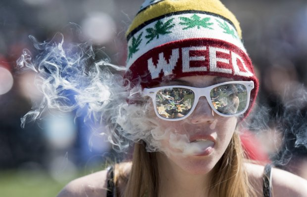 A woman exhales while smoking marijuana during the annual 420 marijuana rally on Parliament Hill in Ottawa, Canada, Wednesday, April 20, 2016. Cannabis possession is illegal in most countries under a 1925 treaty called the International Opium Convention. But just like the U.S., some nations either flout the treaty or don't enforce it. Legalization supporters consider pot possession either legal or tolerated in Argentina, Bangladesh, Cambodia, Canada, Chile, Colombia, the Czech Republic, India, Jamaica, Jordan, Mexico, Portugal, Spain, Uruguay, Germany and the Netherlands. (Justin Tang/The Canadian Press via AP) MANDATORY CREDIT