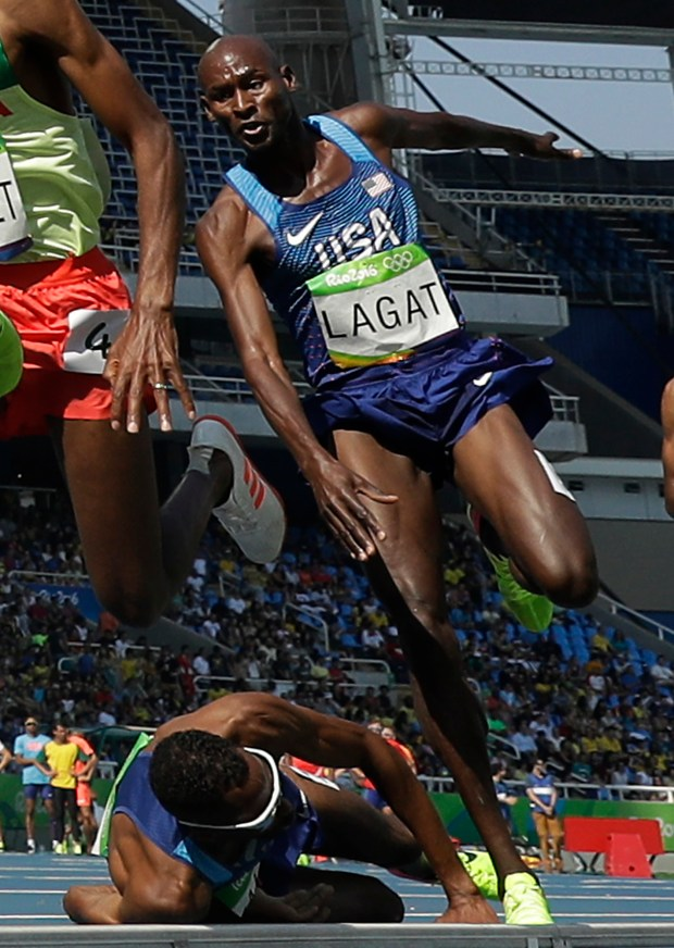 United States' Bernard Lagat leaps over United States' Hassan Mead who fell in a men's 5000-meter heat during the athletics competitions of the 2016 Summer Olympics at the Olympic stadium in Rio de Janeiro, Brazil, Wednesday, Aug. 17, 2016. (AP Photo/Matt Dunham)