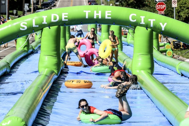 People slide down the nearly 1,000-foot long water slide on 12th Avenue East in Duluth during the Slide the City event Saturday afternoon. (Clint Austin / caustin@duluthnews.com)