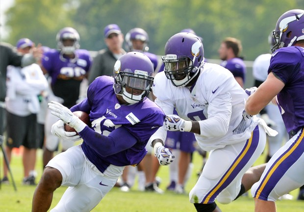 Minnesota Vikings defensive end Zach Moore gets a piece of running back Jhurell Pressley's jersey in a scrimmage during training camp at Minnesota State University in Mankato on July 31, 2016. (Pioneer Press: John Autey)