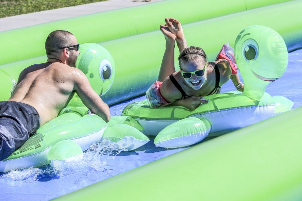 Tony Lutterman, left, and Sacia Vieregge both of Hudson, Wis. slide on inflatable turtles during the Slide the City event on 12th Avenue East in Duluth Saturday afternoon. (Clint Austin / caustin@duluthnews.com)