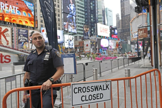 A police officer stands guard at a section of Times Square closed off to pedestrians after the bombing in the Chelsea neighborhood, Sunday, Sept. 18, 2016, in New York. Gov. Cuomo said 1,000 additional law enforcement officers were being deployed after the Saturday night blast in Chelsea, a primarily residential neighborhood on Manhattan's west side that's known for its art galleries and large gay population. He encouraged New Yorkers to go about their day as usual.(AP Photo/Mary Altaffer)