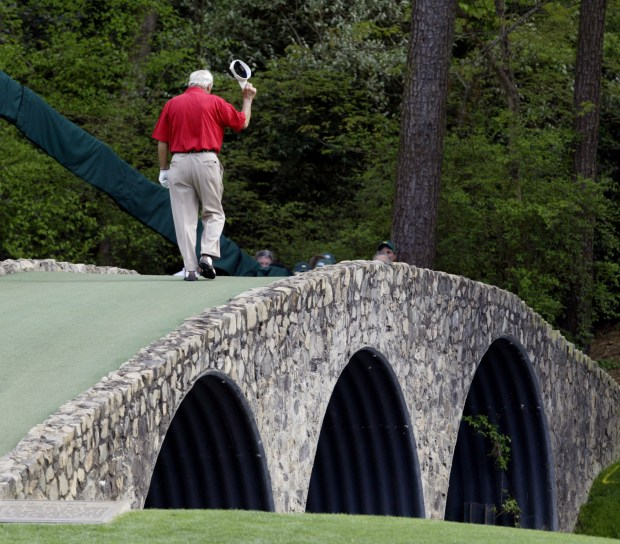 This April 9, 2004, file photo shows Arnold Palmer walking across the Hogan Bridge on the 12th fairway for the final time in Masters competition during the second round of the Masters golf tournament at the Augusta National Golf Club in Augusta, Ga. (AP Photo/Amy Sancetta, File)
