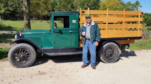 """The late Edward """"Flaming Eddie"""" Erickson poses with his prized 1928 Chevy Capitol truck in this undated photo taken at his farm in Scandia, Minn. Erickson died in April at the age of 78; the truck and thousands of other antiques he collected will be sold at auction on Sept. 10, 2016. Photo courtesy of the Erickson family."""