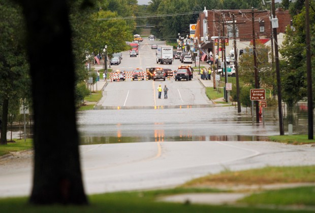 Main Street near Covered Bridge Park in Zumbrota, Minn., is blocked off Thursday morning, Sept. 22. 2016, following flooding, which was the result of 5 inches of rain. Heavy rain has flooded homes, closed major highways, stranded motorists and derailed a train in several Midwestern states. (Elizabeth Nida Obert/Post-Bulletin via AP)