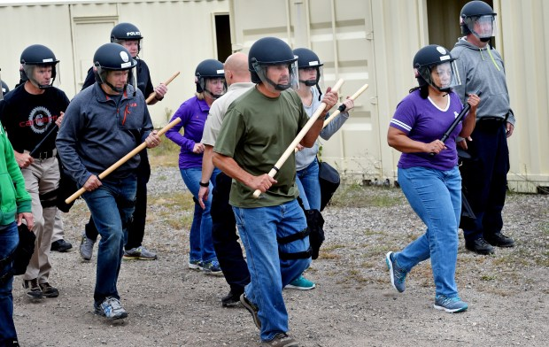 Metro area law enforcement heads into a group of pretend protesters Thursday, Sept. 15, 2016 at the Arden Hills Army Training Site in Arden Hills as the St. Paul police beef up their protests and large-scale demonstrations skills to insure protester safety, officer safety and security of the area. (Jean Pieri / Pioneer Press)