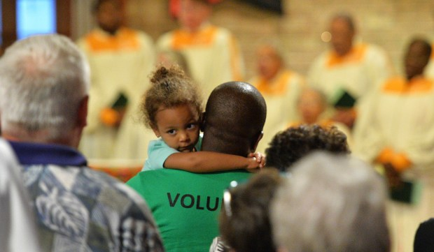 Charlotte Banteh, 3, holds on to her dad, Brendan Banteh of Minneapolis, during the Day of Prayer for Unity and Peace at the Church of St. Peter Claver in St. Paul on Thursday, Sept. 8, 2016. Banteh sings in the choir at St. Peter Claver. (Pioneer Press: John Autey)