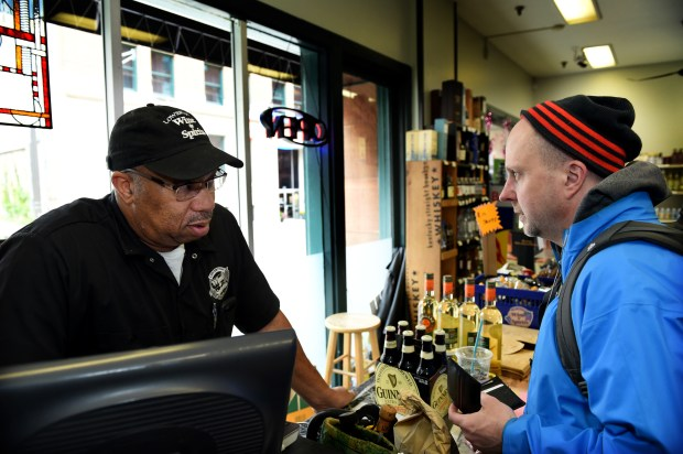 Jerry Blakey, left, owner of Lowertown Wine & Spirits in St. Paul talks to customer Jon Bourgo as he buys Guinness beer Wednesday, Oct. 12, 2016. (Pioneer Press: Jean Pieri)