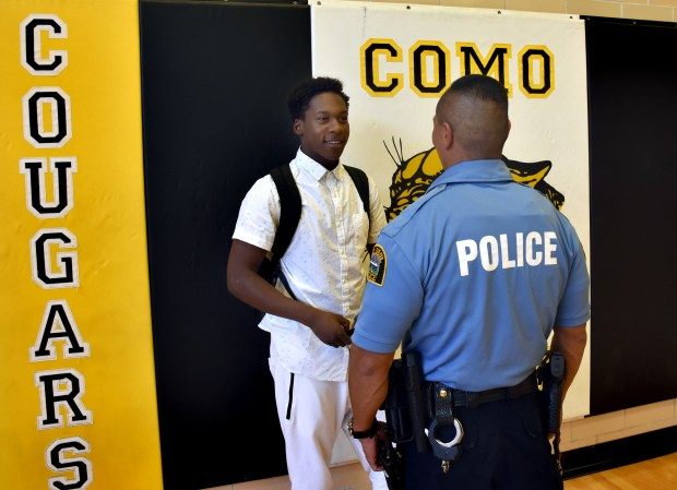St. Paul police officer Toy Vixayvong, right, who works as the Como Park Senior High school resource officer, speaks with Ali Bility at the school on Tuesday, Oct. 25, 2016. Vixayvong has been a mentor to Bility, who struggled with depression. (Pioneer Press: Mara H. Gottfried)