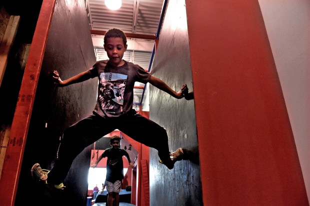 Wallace Agoye, 8, does the spider walk at Conquer Ninja Warrior in Woodbury on Friday, Oct. 21, 2016. The gyms are designed to look like the show sets, with padded slides, climbing walls and dangling straps, all in cartoonishly bright colors. (Pioneer Press: Jean Pieri)