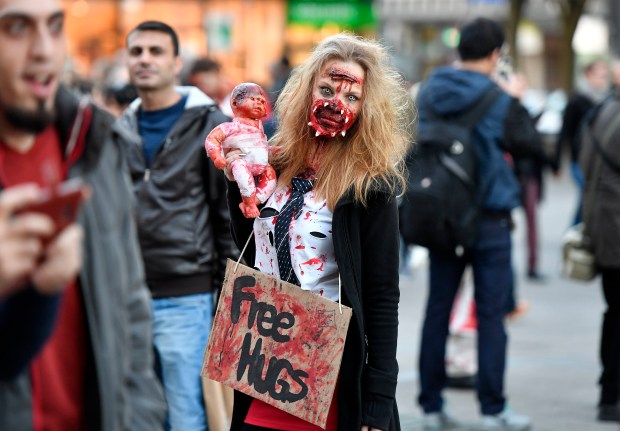 A woman dressed in a Halloween costume poses for a photo before participating in the zombie walk in Essen, Germany, Monday, Oct. 31, 2016. (AP Photo/Martin Meissner)