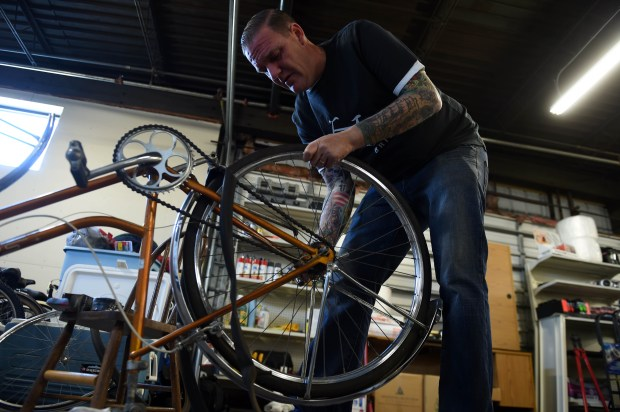 J.P Liesenfeld replaces a worn out tire on a donated bike which he will ship to Jamaica and hand out for free, in a Minneapolis warehouse, Tuesday, Oct. 11, 2016. (Pioneer Press: Scott Takushi)