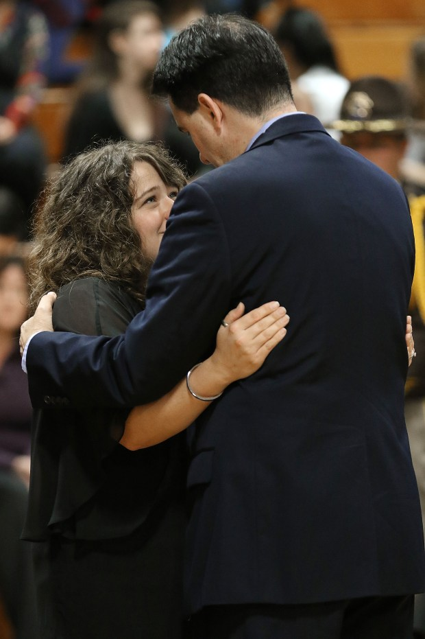 Wisconsin Gov. Scott Walker embraced Sarah Glaze, wife of Rusk County Deputy Sheriff Dan Glaze Jr., during a visitation for Glaze Jr., Friday, Nov. 4, 2016 at the former Cameron Elementary School in Cameron, Wis. Douglas Nitek is accused of killing Glaze Saturday night, Oct. 29, as the officer investigated a report of a suspicious vehicle in a field several miles from the suspect's residence near Ladysmith, about 130 miles northeast of Minneapolis. (Dan Reiland/The Eau Claire Leader-Telegram via AP) MANDATORY CREDIT