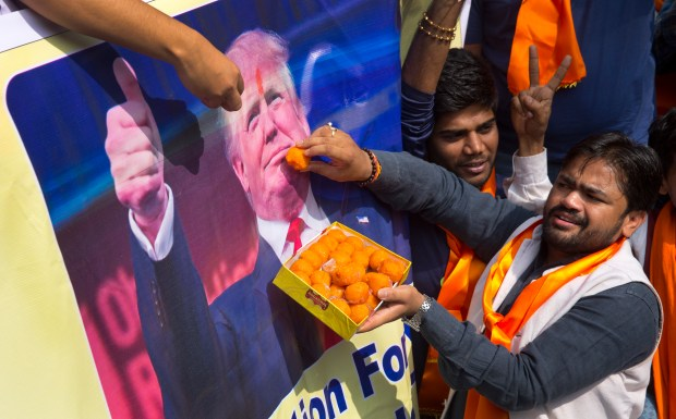 Activists belonging to 'Hindu Sena' or Hindu Army, a local organization offer sweets symbolically to US presidential candidate Donald Trump's poster in anticipation of his victory in New Delhi, India, Wednesday, Nov. 9, 2016. (AP Photo/Manish Swarup)