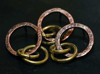 The copper pins with three intertwining rings honor slain Saudi student Hussain Saeed Alnahdi and symbolize that the University of Wisconsin-Stout and community are united in sadness and a commitment to prevent similar acts of violence. (University of Wisconsin-Stout)