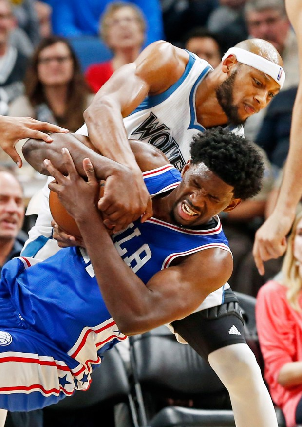 Minnesota Timberwolves' Adreian Payne, top, tries to wrestle the ball from Philadelphia 76ers' Joel Embiid of Cameroon in the second half of an NBA basketball game Thursday, Nov. 17, 2016, in Minneapolis. The Timberwolves won 110-86. (AP Photo/Jim Mone)