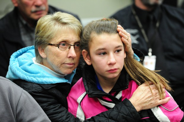 Beth Birr comforts her granddaughter Fran Brisk at a press conference Wednesday, Dec. 7, 2016, to appeal to the public for any information in the fatal shooting of Fran's father, Terry Brisk, on Nov. 7. The Morrison County sheriff announced that the shooting of the deer hunter is now a homicide investigation. (Forum News Service: Steve Kohls)