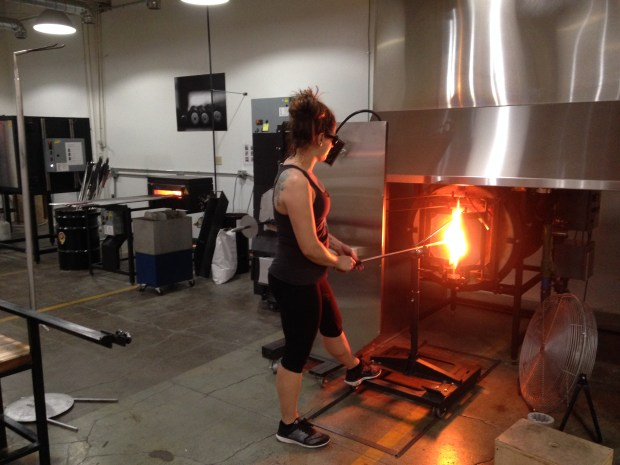 Vandalia Glassworks studio manager Rachel Masica at work making a pint glass. (Richard Chin)