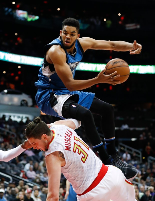 Minnesota Timberwolves center Karl-Anthony Towns (32) is fouled by Atlanta Hawks forward Mike Muscala (31) as he drives to the basket in the second half of an NBA basketball game Wednesday, Dec. 21, 2016, in Atlanta. Minnesota won 92-84. (AP Photo/John Bazemore)