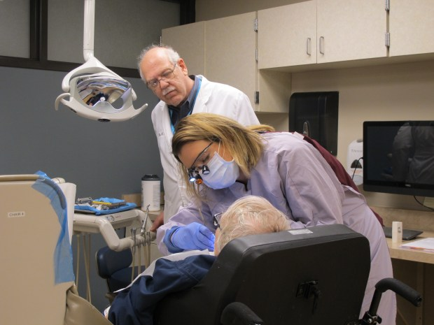 Stephen Shuman, University of Minnesota School of Dentistry associate professor, and dental hygiene student Amy Arcand with a patient at the Walker Methodist Dental Clinic. (Courtesy of Stephen Shuman)