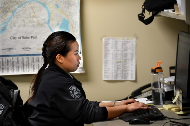 Mai See Her, the state's first Hmong female fire inspector, writes a report and a correction order and sends it out to the responsible party after she inspects and takes a photo of an emergency fire department keybox at an apartment in St. Paul on Thursday, Feb. 9, 2017. The door on the keybox was missing and there was no key in it. (Pioneer Press: Jean Pieri)