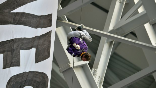One of two protesters who hung a banner demanding that U.S. Bank divest from the North Dakota Access Pipe Line descends, Spider Man style down his rope the second quarter at U.S. Bank Stadium on Sunday, Jan 1, 2017. (Pioneer Press: John Autey)