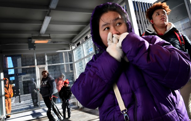 Naw Naw tries to stay warm as she waits for a bus home on Fifth Street in St. Paul on Wednesday, Jan. 4, 2017. The forecast is for highs in the single digits through Saturday. (Pioneer Press: Jean Pieri)