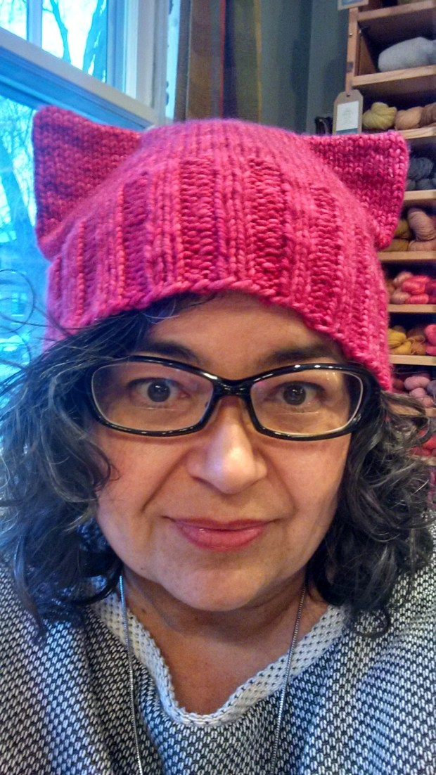 "This January 2017 photo provided by Angie Paulson, shows Paulson, a knitter who works at The Yarnery shop in Saint Paul, Minn., as she displays one of the ""pussy"" hats she made as part of a call to action answered by thousands of knitters to supply marchers at the Women's March in Washington, D.C., on Jan. 21 with warm head gear and a way to show their solidarity for women's rights. (Angie Paulson via AP)"