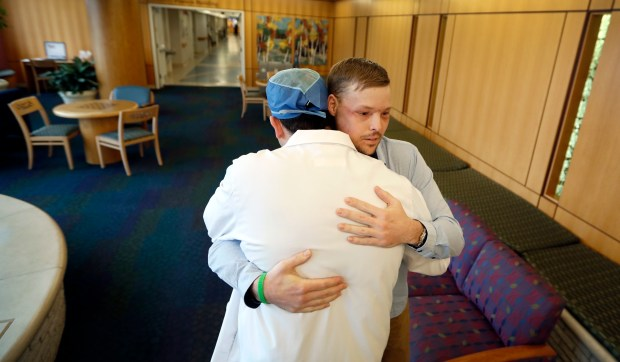 In this Jan. 25, 2017, photo, face transplant recipient Andy Sandness is hugged by Dr. Samir Mardini, foreground, during a visit to the Saint Marys Hospital campus at the Mayo Clinic in Rochester, Minn. Mardini led a medical team to perform Sandness' face transplant surgery, the first performed at the medical center. (AP Photo/Charlie Neibergall)