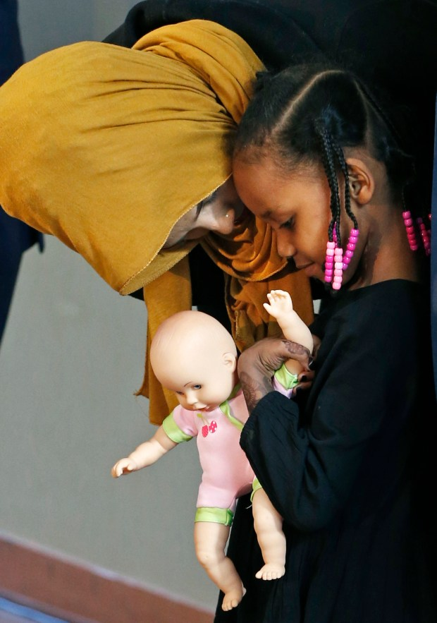 Four-year-old Somali refugee Mushkaad Abdi, right, holds a doll as her mother, Samira Dahir, talks with her at a Minneapolis news conference Friday, Feb. 3, 2017, one day after she was reunited with her family. Her trip from Uganda to Minnesota was held up by President Donald Trump's Jan. 27 order barring refugees from seven predominantly Muslim nations. (AP Photo/Jim Mone)