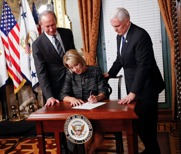 Vice President Mike Pence, right, watches as newly sworn-in Education Secretary Betsy DeVos signs the affidavit of appointment in the Eisenhower Executive Office Building n Washington, Tuesday, Feb. 7, 2016. DeVos' husband Dick DeVos is at left. (AP Photo/Pablo Martinez Monsivais)