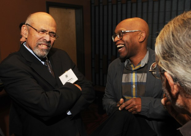 Penumbra Theatre founder and artistic director Lou Bellamy, left, shares a laugh with set designer and friend of the theatre, Seitu Jones, in the lobby before a special program at Penumbra Theatre in St. Paul on Jan. 13, 2014. At right is theatre supporter Bill Drake. (Pioneer Press: Scott Takushi)