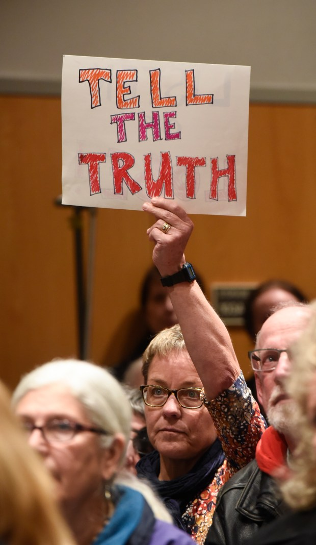 An audience member holds a sign during a town hall meeting held by U.S. Rep. Tom Emmer in Sartell, Minn., Wednesday, Feb. 22, 2017. Emmer's town hall went on as planned after the congressman said he would shut down the event if protests or unruly attendees disrupted the conversation. (Dave Schwarz/St. Cloud Times via AP)